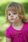 Little girl in pink with muddy face Stock Image