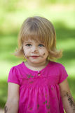Little girl in pink with muddy face. Little girl outside with pink top and muddy face stock photography