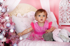 Little girl in pink near the Christmas tree. Stock Photography