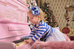 Little girl with a pink piano Stock Images