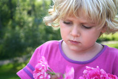 Little girl with pink pion. A blond serious little girl in a garden, looking at pions. Horizontal Stock Photography