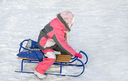 Little girl in pink playing on a toboggan Royalty Free Stock Image