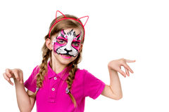 Little girl in pink posing with painted mask on face Royalty Free Stock Photo