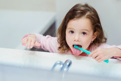 Little girl in pink pyjamas in bathroom brushing teeth. Cute little girl in pink pyjamas in bathroom brushing her teeth Royalty Free Stock Photography