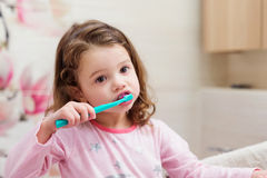Little girl in pink pyjamas in bathroom brushing teeth. Cute little girl in pink pyjamas in bathroom brushing her teeth Royalty Free Stock Photos