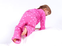 Little girl in pink pyjamas climbing on bed Royalty Free Stock Images