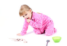 Little girl in pink pyjamas eating cereal Stock Photography