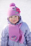 Little girl in pink scarf and hat smiles and looks at camera Royalty Free Stock Photography