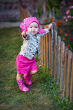 Little girl in pink shoes near the fence.  Stock Photos