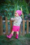 Little girl in pink shoes near the fence.  Royalty Free Stock Photos