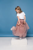 Little girl in pink skirt posing in studio Royalty Free Stock Images