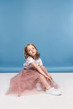 Little girl in pink skirt sitting on floor and looking at camera Stock Photos