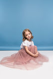 Little girl in pink skirt sitting on floor and looking at camera Royalty Free Stock Photo