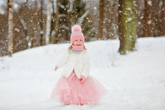 Little girl in a pink skirt in winter smiles in the park Stock Photography