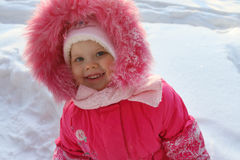 Little girl in pink stands and smiles in winter Royalty Free Stock Photography
