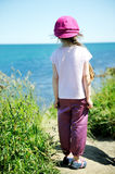 Little girl in pink sun hat looking upon ocean Royalty Free Stock Images