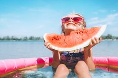 Little girl in pink sunglasses with bid watermelon segment funny royalty free stock images
