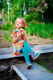 Little girl in pink sunglasses sitting and eating ice cream Stock Image