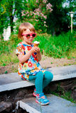 Little girl in pink sunglasses sitting and eating ice cream Royalty Free Stock Photos