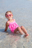Little girl in pink swimsuit and sunglasses sitting in the sea posing at camera. Happy, smiling. Summer vacation. Stock Images