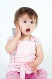 Little girl in pink talking by mobile. Isolated on white Stock Photo