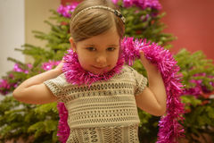 Little girl with pink tinsel on a neck standing near a fir-tree laughs Royalty Free Stock Photography