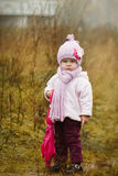 Little girl  with pink umbrella in autumn park Stock Photo