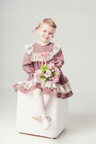 Little girl in pink-violet dress and bouquet flowers Stock Photo