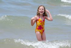 Laughing girl playing in waves. A little girl in a pink and yellow bathing suit, laughs as she plays in the waves on lake Michigan while on a summer vacation Royalty Free Stock Photos