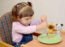 The little girl pins sausage on a fork Stock Photography