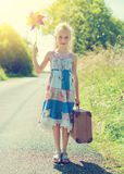 Little girl with pinwheel on rural road. Stock Photography