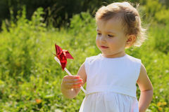 Little girl with pinwheel standing in grass Stock Images