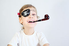 Little girl with pipeful and bandaged eye is pirate. Royalty Free Stock Image
