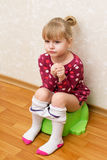 Little girl on the potty. Little girl is sitting on the green children's potty, loose tights stock photography