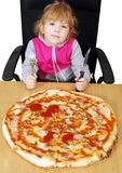 Little girl with pizza Stock Photos