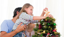 Little girl placing a star in a Christmas tree Royalty Free Stock Images