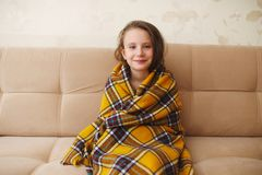Little girl with plaid at home. Photo of little girl with plaid at home Stock Photo