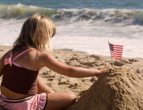 Little Girl planting flag in sand. A little girl planting a united states of america flag in the sand on a sunny day at the beach Royalty Free Stock Images