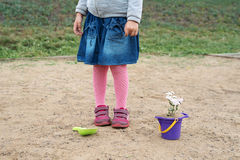 Little girl planting a flower in a sand-box. Royalty Free Stock Photos