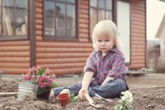 Little girl planting and watering flowers in garden Stock Photo