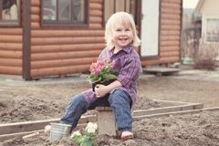 Little girl planting and watering flowers in garden Stock Photos