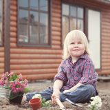 Little girl planting and watering flowers in garden Stock Images