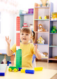 Little girl play with building bricks in preschool. Cute little girl excited with tall column she built using building bricks in preschool stock photography