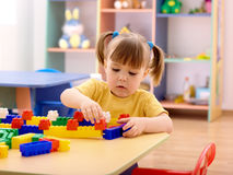 Little girl play with building bricks in preschool Stock Photos