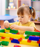 Little girl play with building bricks in preschool Stock Image