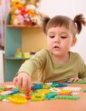 Little girl play with building bricks in preschool. Cute little girl play with building bricks in preschool stock photo