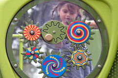 Little girl play with colorful wheels in the playground. Little girl (Age 04) play with colorful wheels in the playground. Concept photo of child, childhood Royalty Free Stock Photography
