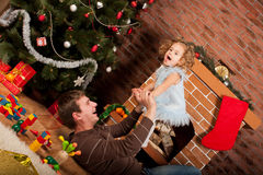 Little girl play with dad  near Christmas tree Stock Photography