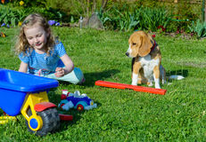 Little girl play with dog in the garden royalty free stock images