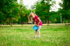Little girl play with flying disk in motion, playing leisure activity games. In summer park stock photography